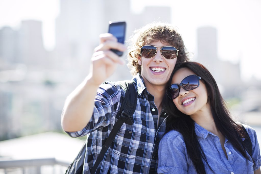 USA, Washington, Seattle, Couple wearing sunglasses photographing themselves with smart phone : Stock Photo