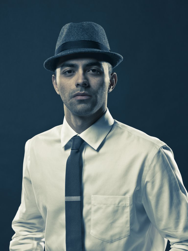 Studio portrait of young man wearing tie and hat : Stock Photo