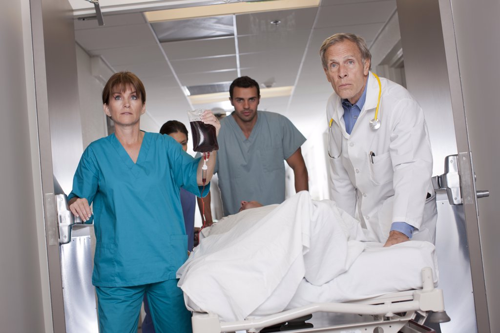 Stock Photo: 1795R-59993 Team of doctors wheeling in patient