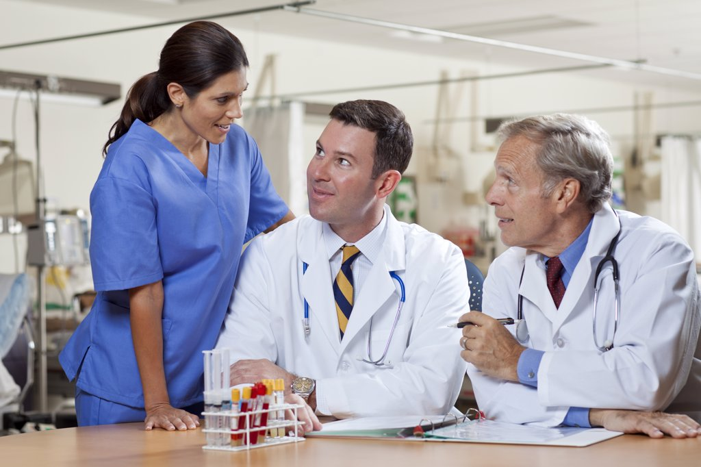 Female surgeon and two male doctors in hospital : Stock Photo