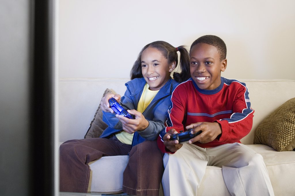 Brother and sister (10-13) playing video game : Stock Photo