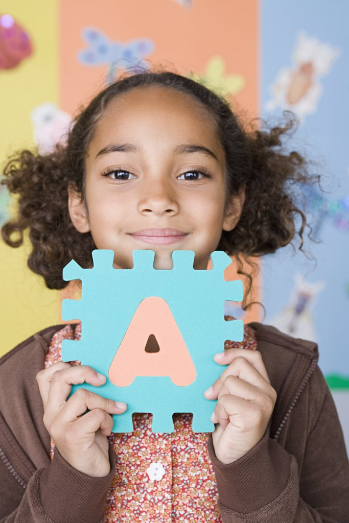 Smiling girl (6-7) holding letter A : Stock Photo