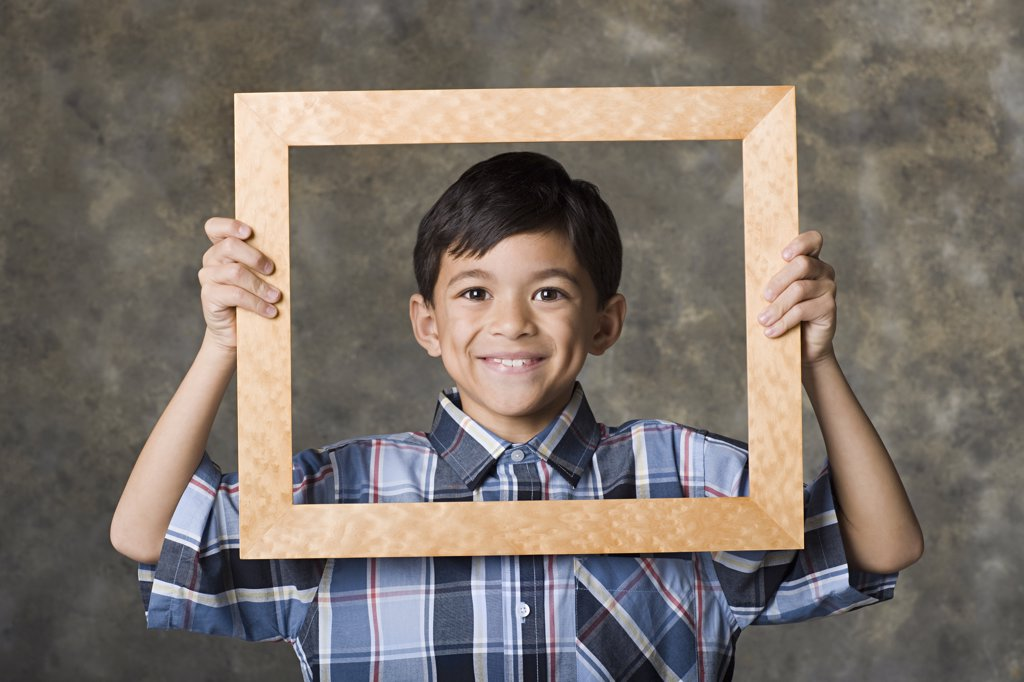 Stock Photo: 1795R-60430 Portrait of smiling boy (8-9) looking through frame, studio shot