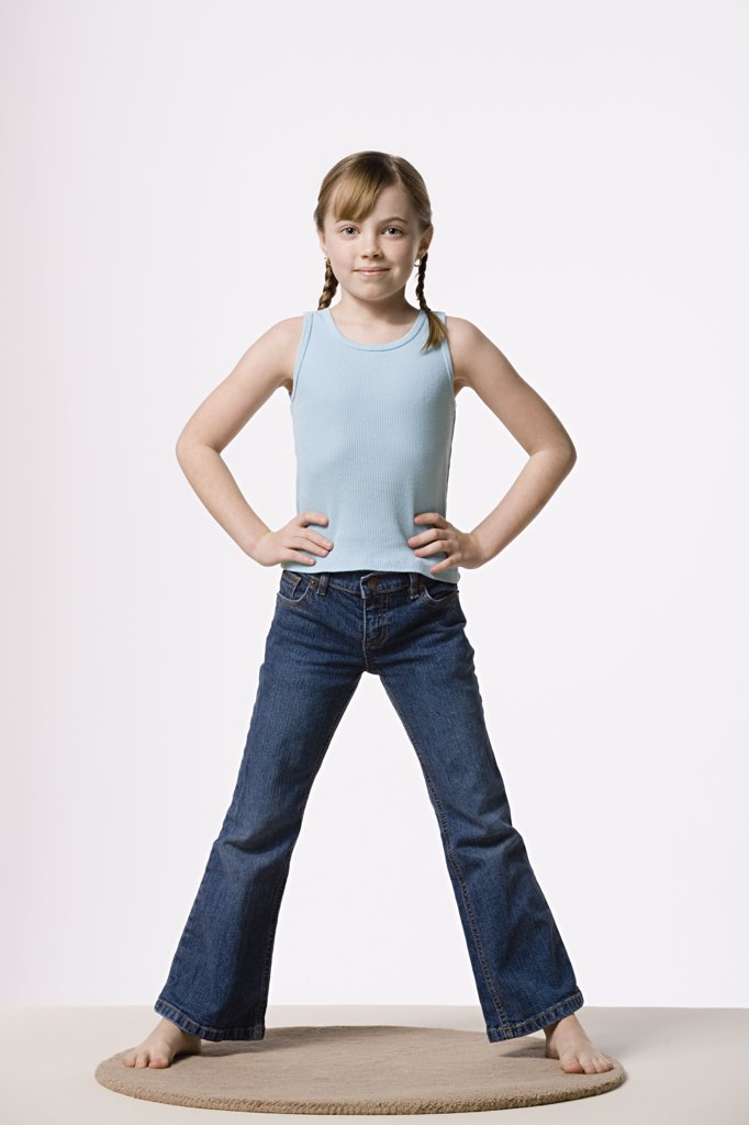 Portrait of girl (8-9) with hands on hips, studio shot : Stock Photo