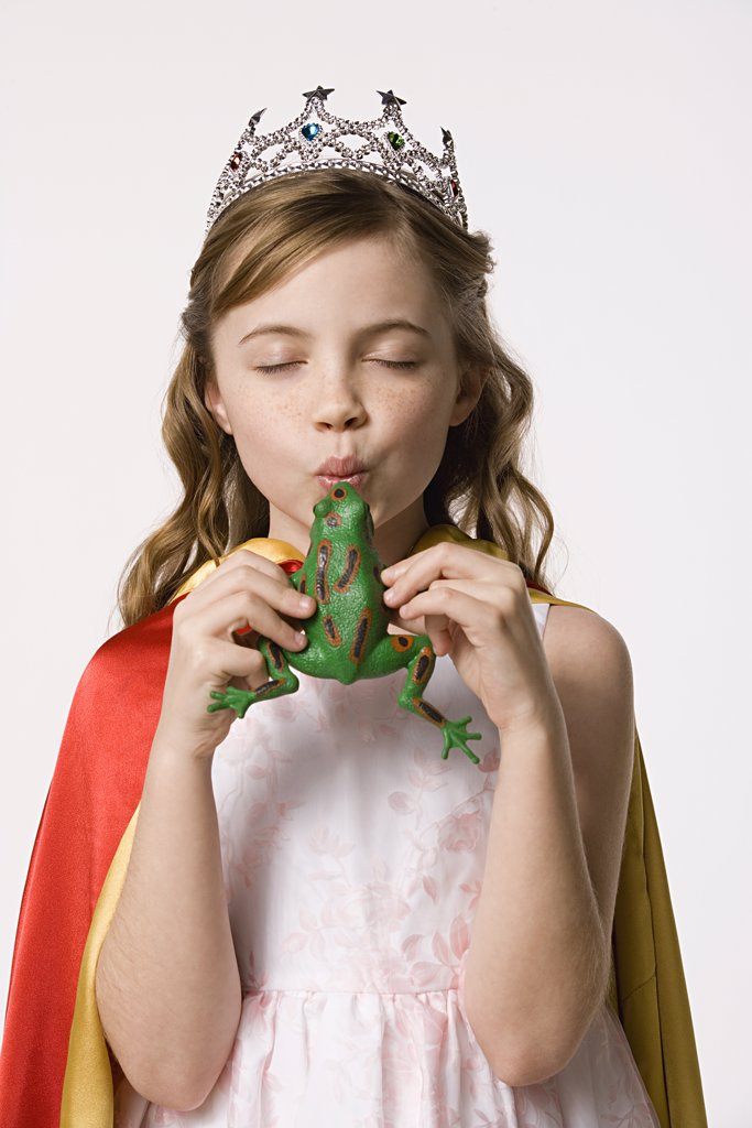 Studio portrait of girl (8-9) wearing princess costume and kissing toy frog : Stock Photo
