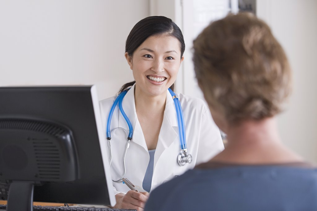 Stock Photo: 1795R-60729 Smiling female doctor talking to patient in her office