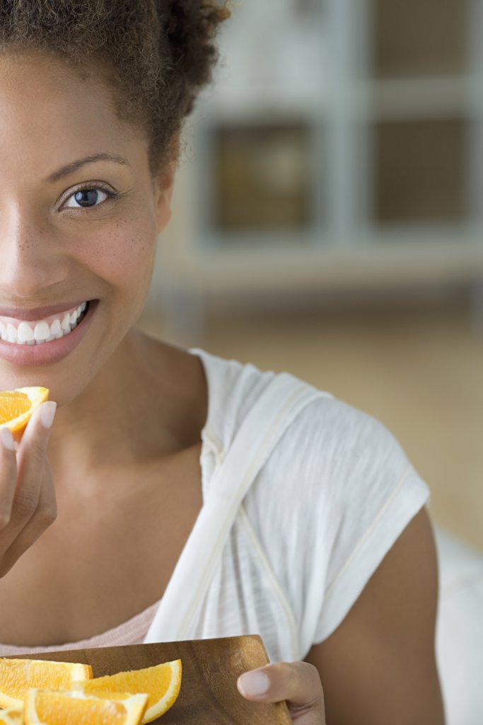 Stock Photo: 1795R-60954 Attractive woman eating orange