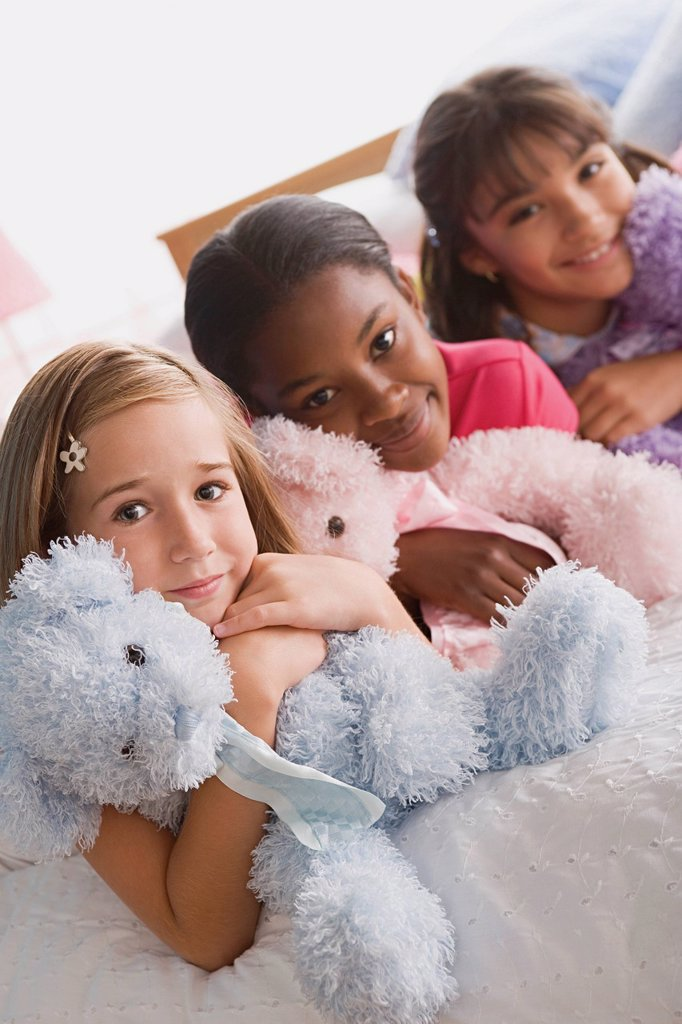 Portrait of three smiling girls (10-11) with puppets in bed : Stock Photo