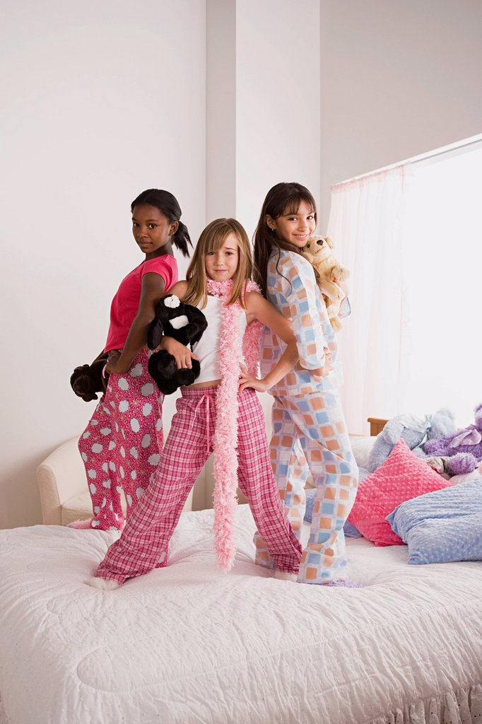 Portrait of three girls (10-11) standing on bed at slumber party : Stock Photo