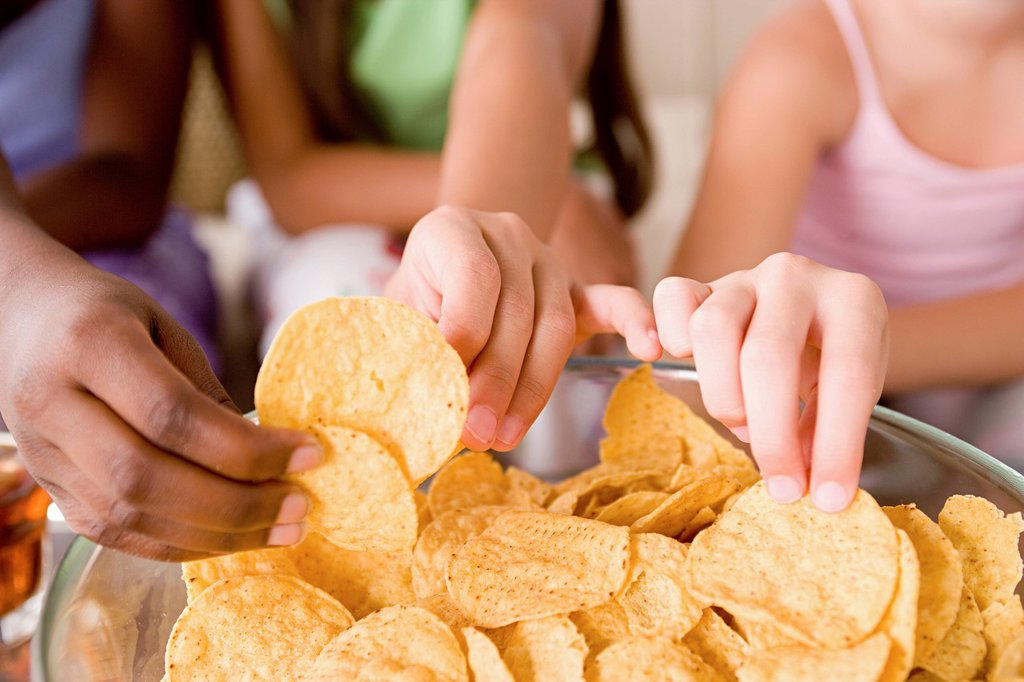 Stock Photo: 1795R-61661 Three girls (10-11) reaching for crisps