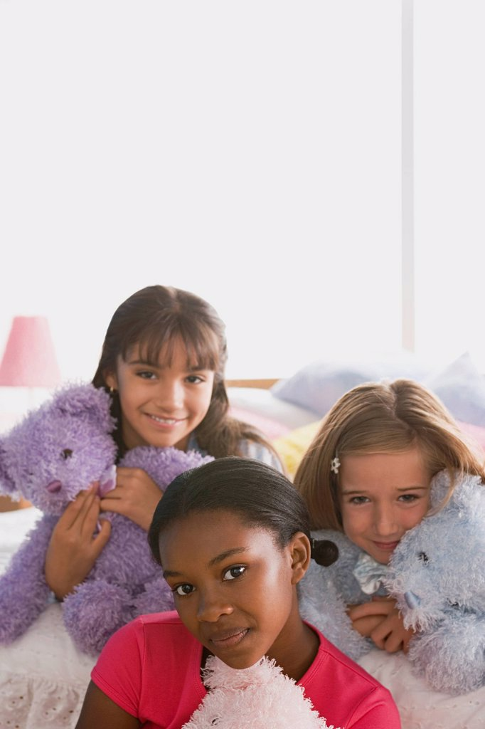 Stock Photo: 1795R-61678 Portrait of three girls (10-11) with puppets in bed