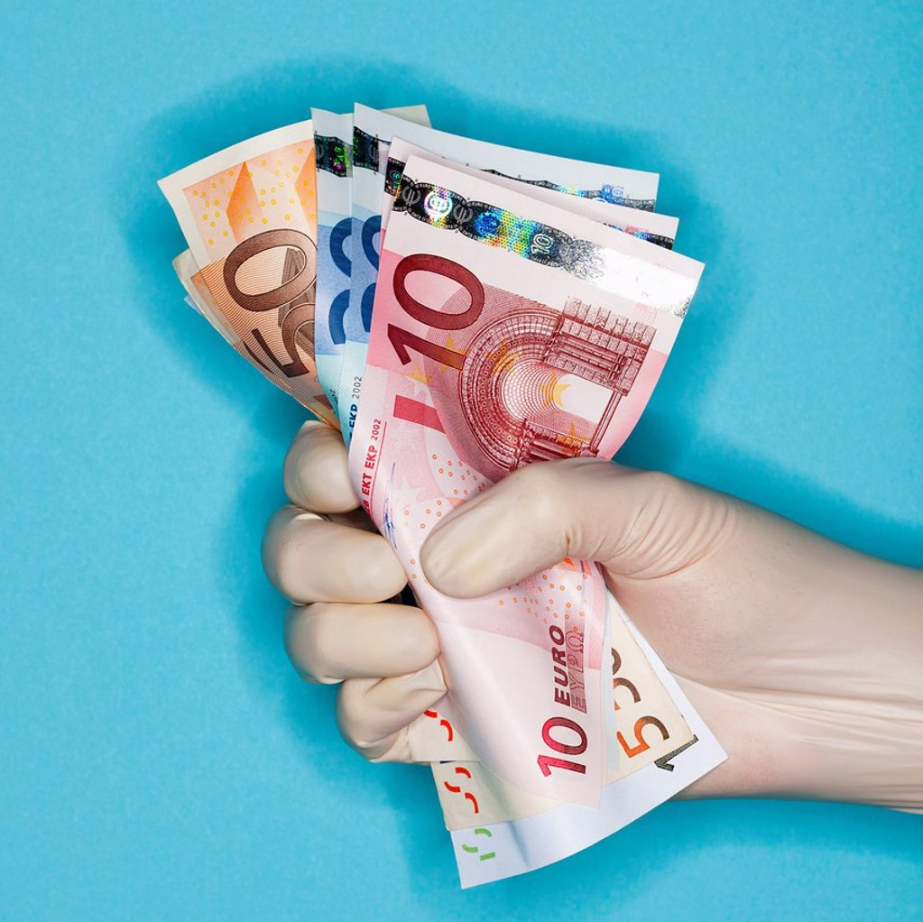 Hand in surgical glove holding banknotes : Stock Photo