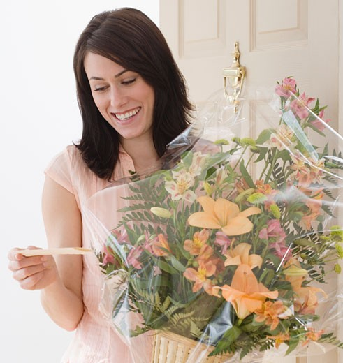 Stock Photo: 1795R-6342 Woman reading card on flower bouquet
