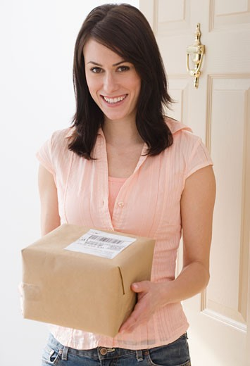 Portrait of woman holding package in doorway : Stock Photo