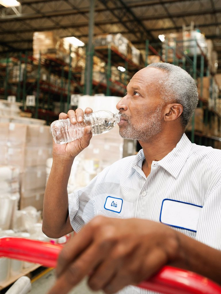 Warehouse worker drinking water : Stock Photo