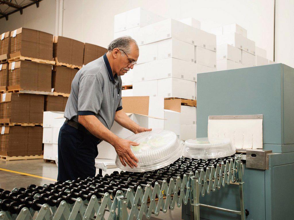 Warehouse worker assembling merchandise : Stock Photo