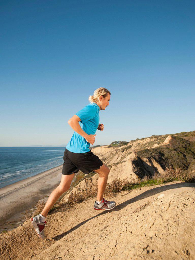 Stock Photo: 1795R-63629 USA, California, San Diego, Man jogging along sea coast