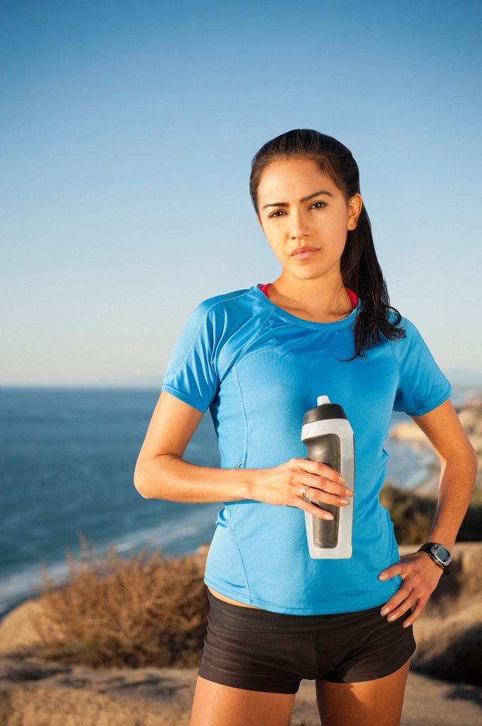 Stock Photo: 1795R-63640 USA, California, San Diego, Portrait of female jogger holding water bottle