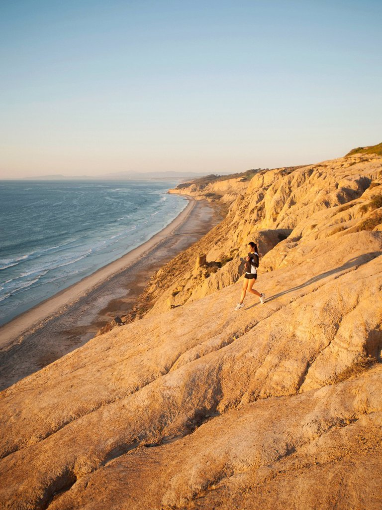 Stock Photo: 1795R-63664 USA, California, San Diego, Woman jogging along sea coast