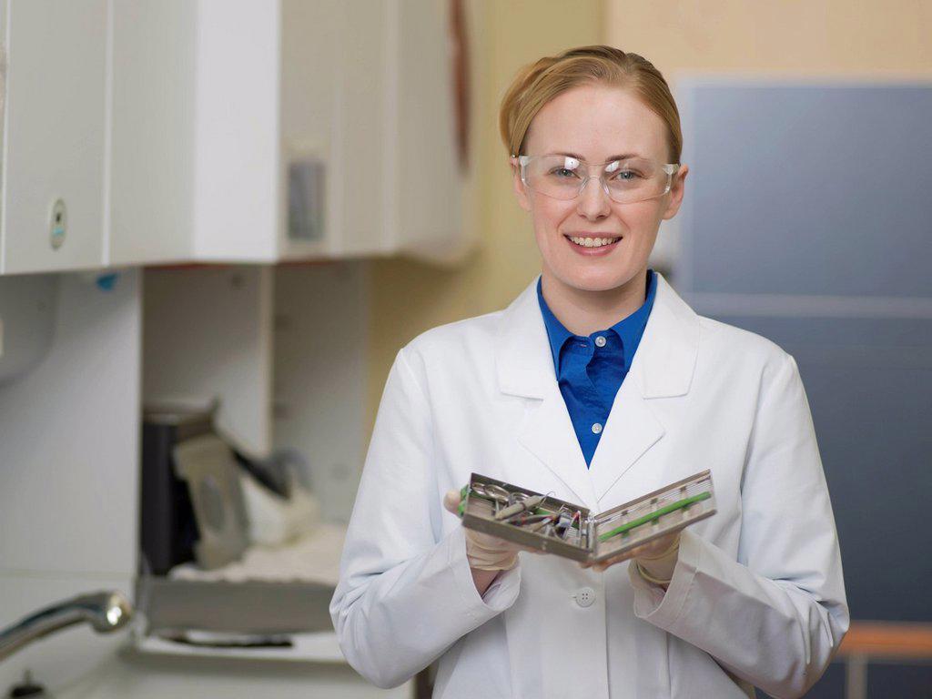 Portrait of dentist holding dental tools : Stock Photo