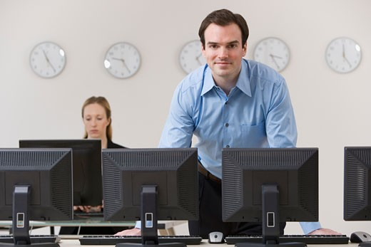 Stock Photo: 1795R-6418 Businessman behind row of computers