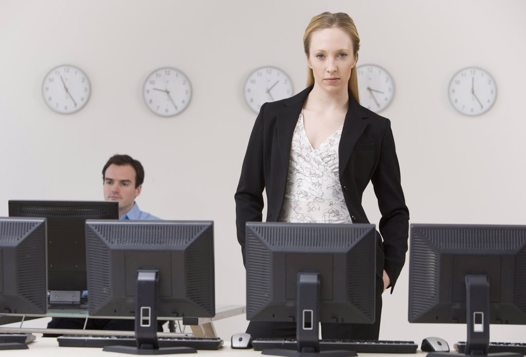 Businesswoman behind row of computers : Stock Photo