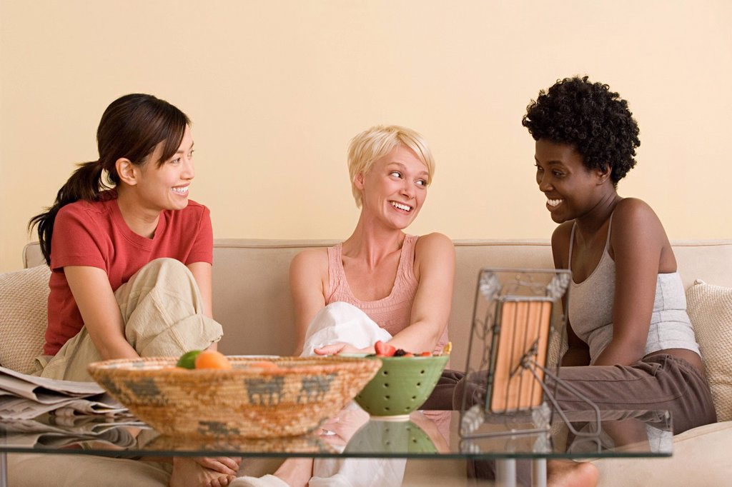 Stock Photo: 1795R-64372 Three female friends sitting on sofa and talking