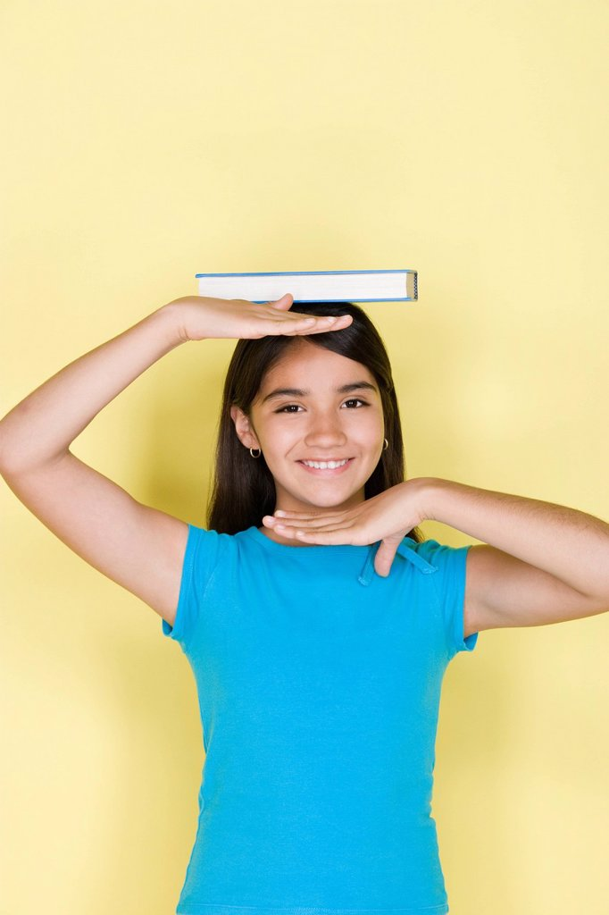 Stock Photo: 1795R-64705 Studio portrait of teenage (16-17) girl balancing book on head