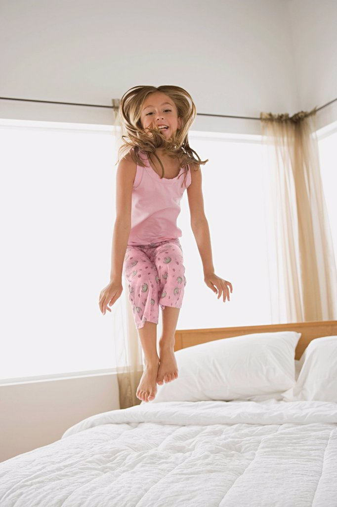 Stock Photo: 1795R-65085 Girl jumping on bed