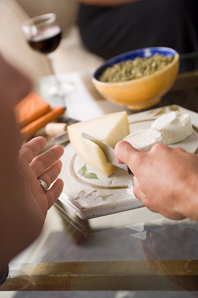 Stock Photo: 1795R-65161 Hand cutting cheese