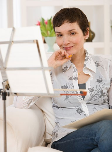 Woman sitting next to sheet music on stand : Stock Photo