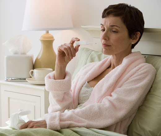 Woman taking own temperature in bed : Stock Photo