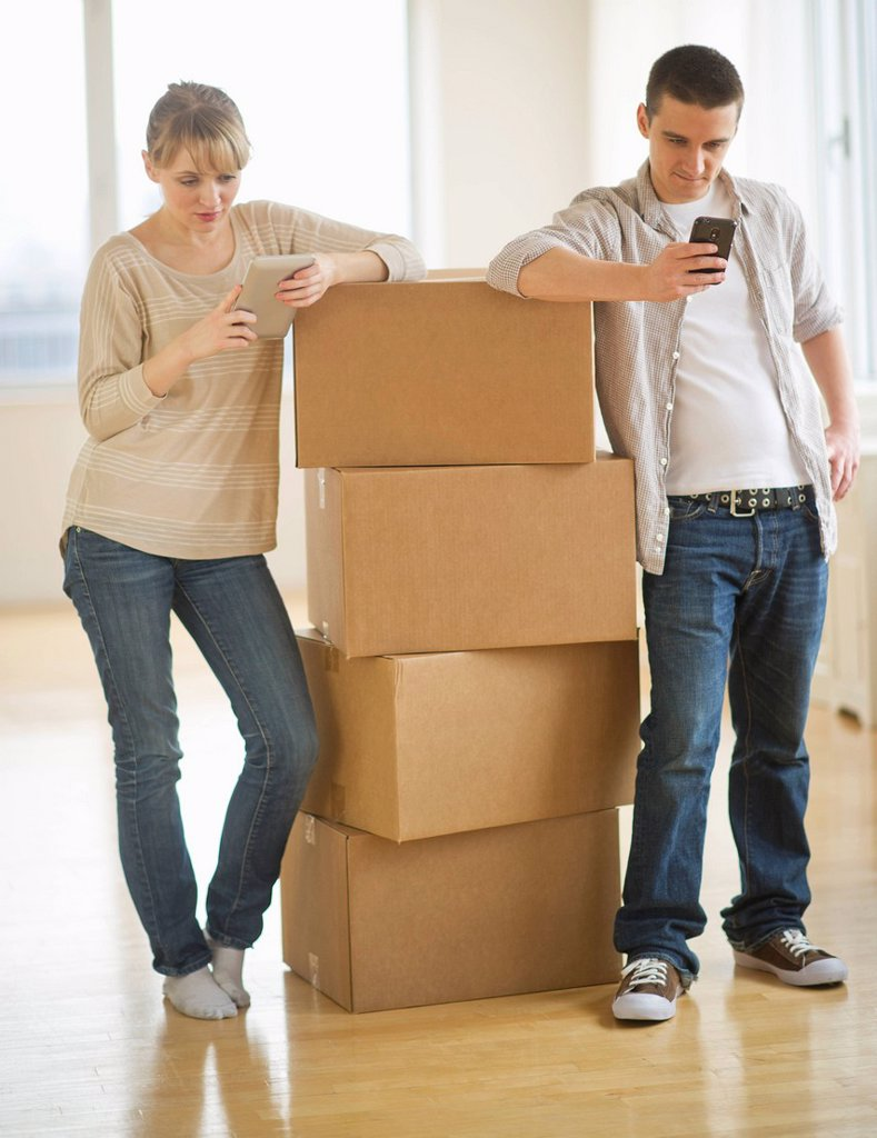 Stock Photo: 1795R-65693 Couple leaning on cardboard boxes during relocation
