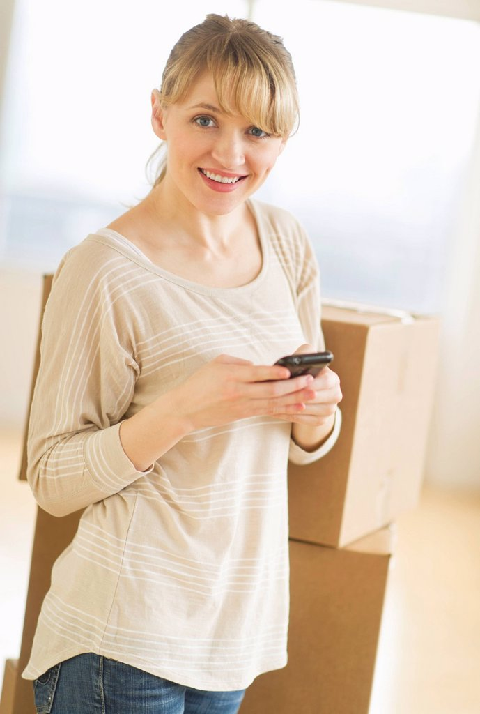 Stock Photo: 1795R-65695 Woman using smart phone during relocation