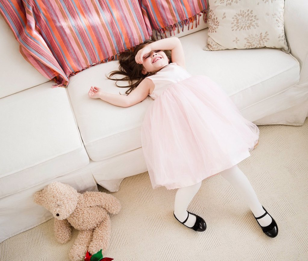 Small girl 4_5 years in tulle dress leaning on sofa : Stock Photo