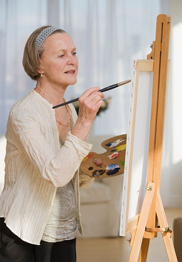 Stock Photo: 1795R-6610 Senior woman painting on easel