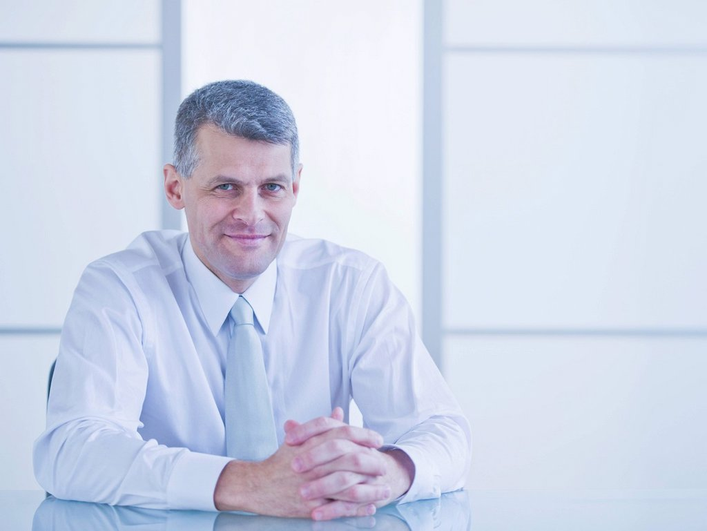Portrait of businessman sitting at desk : Stock Photo