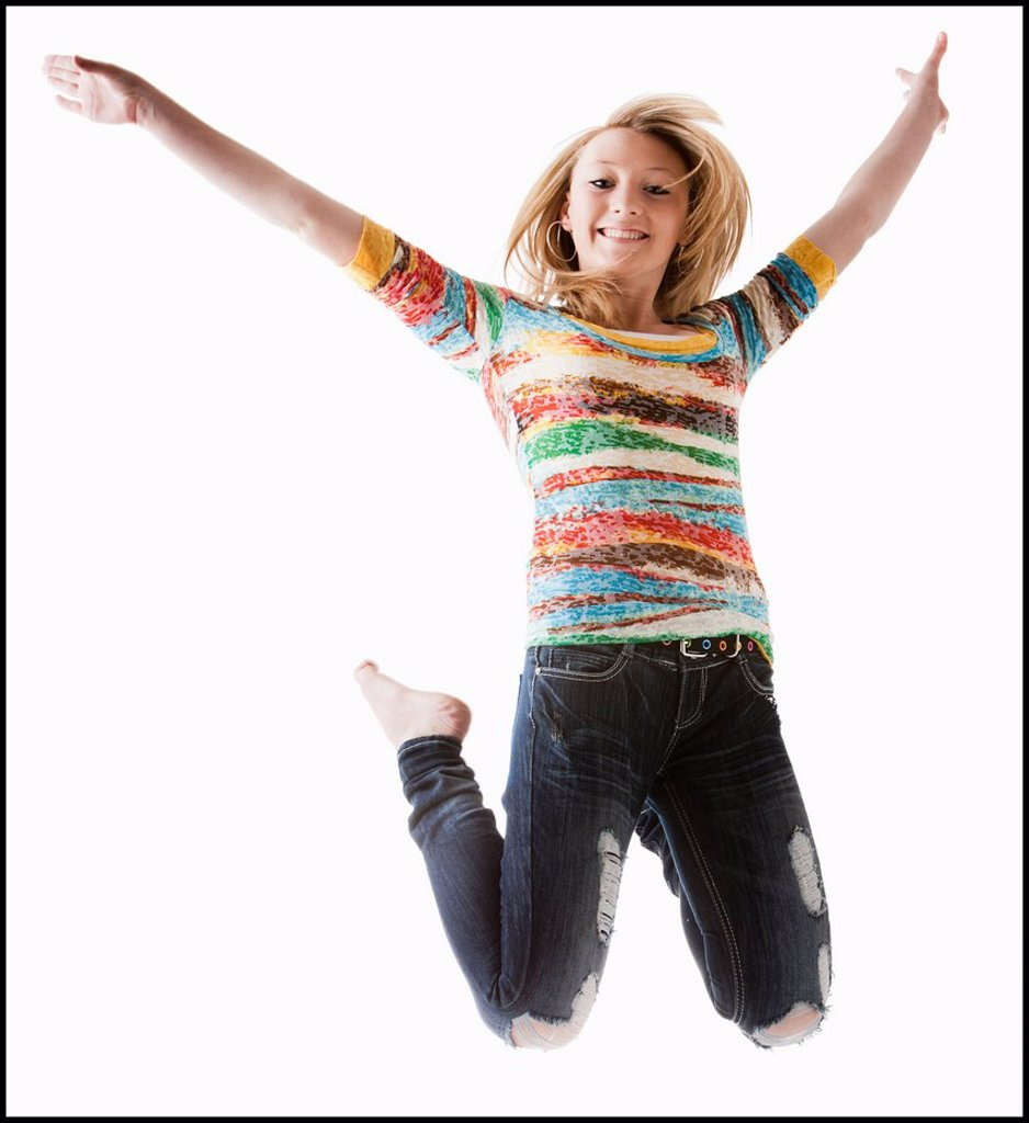 Studio shot of girl 12_13 jumping with arms raised : Stock Photo