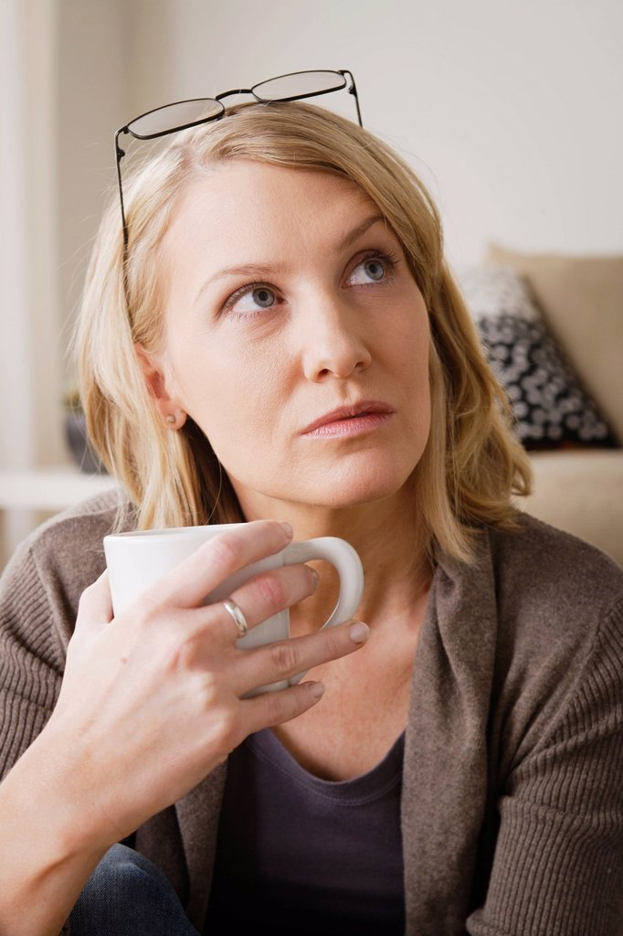 Stock Photo: 1795R-66982 Mid adult woman drinking coffee and looking away