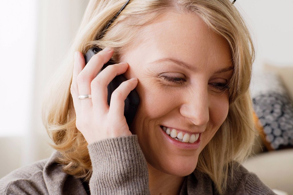 Stock Photo: 1795R-66985 Portrait of smiling mid adult woman talking via mobile