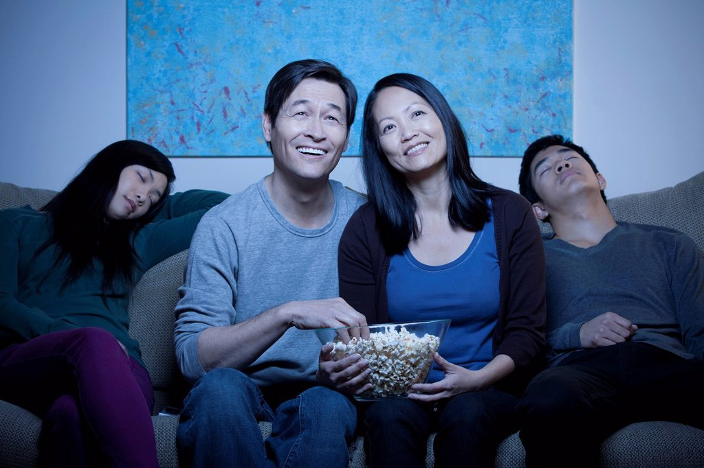 Smiling family watching TV and eating popcorn : Stock Photo
