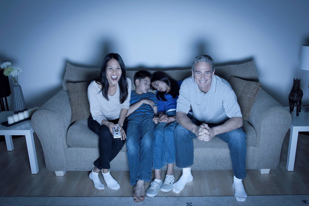 Family sitting on sofa and watching television : Stock Photo