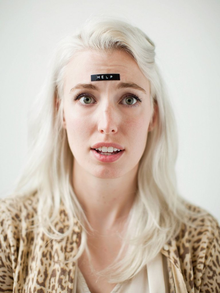 Stock Photo: 1795R-67878 Portrait of young woman with word help on forehead
