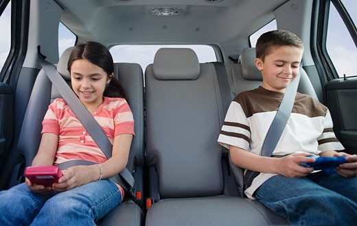 Brother and sister playing video games in car : Stock Photo