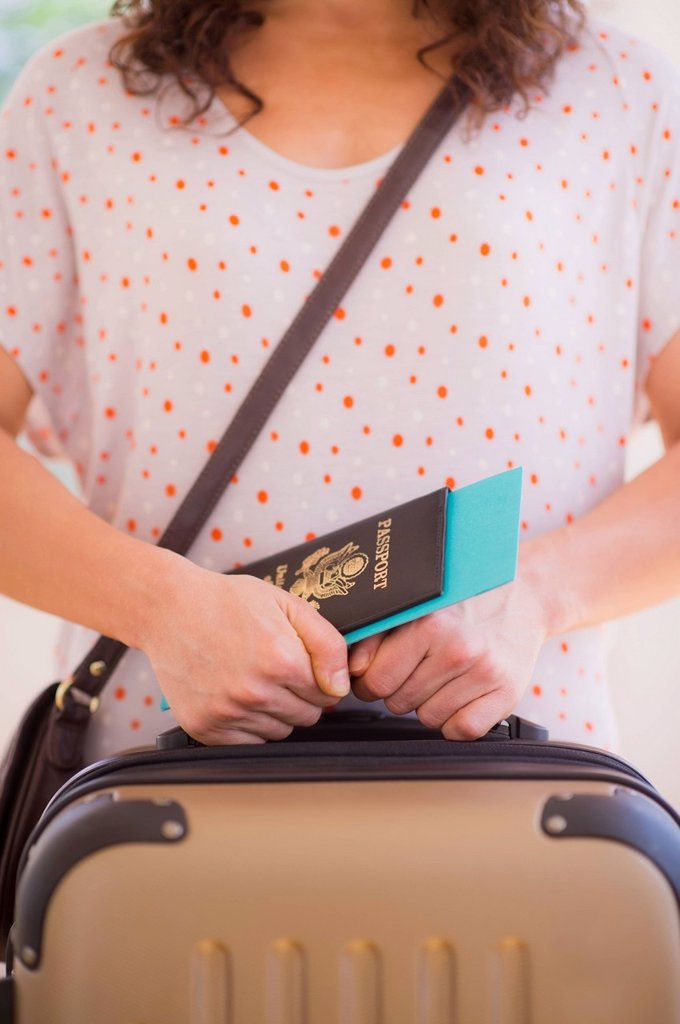 Stock Photo: 1795R-69128 Close up of woman holding luggage and passport