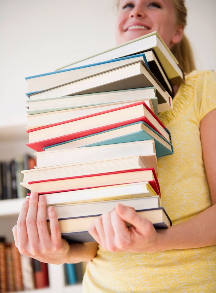 Stock Photo: 1795R-69517 Woman carrying stack of books