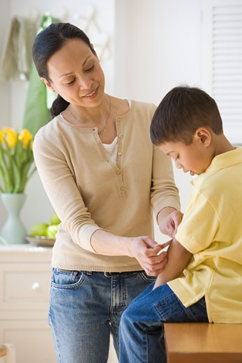 Stock Photo: 1795R-6989 Asian mother putting bandage on son