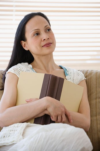 Asian woman holding book on sofa : Stock Photo