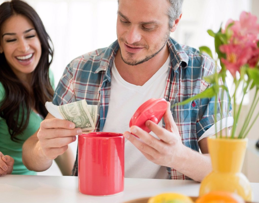 Stock Photo: 1795R-70093 Couple putting money in savings jar