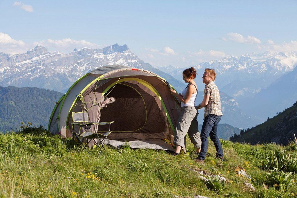 Stock Photo: 1795R-70105 Switzerland, Leysin, Hikers pitching tent on meadow